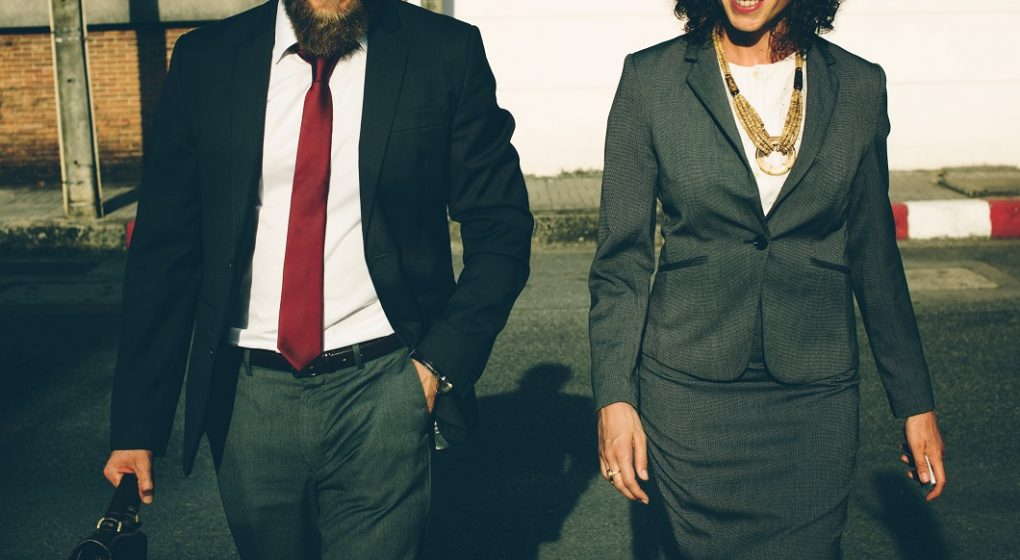 Man and lady are walking across the road looking professional in outfits