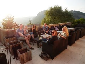 Group sitting on a balcony in France with a lovely mountain view with sun streaming in