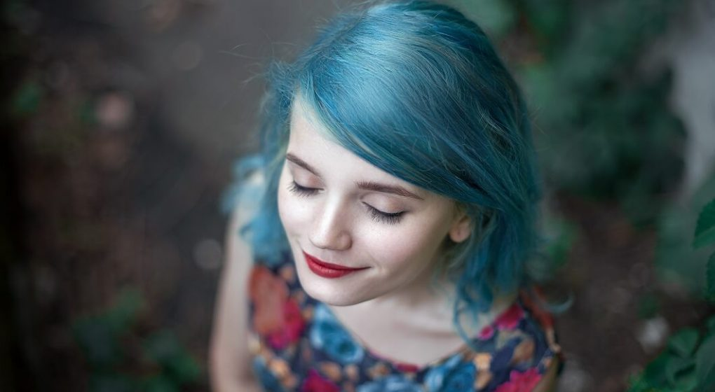 Lady with blue hair and red lipstick looking up with eyes closes